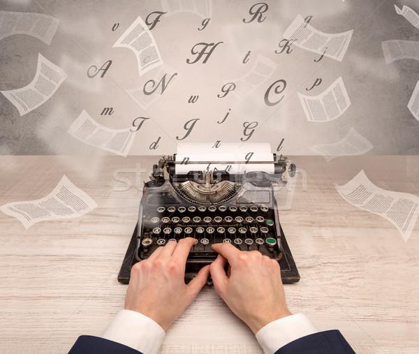 Hand typewriting with flying documents around Stock photo © ra2studio