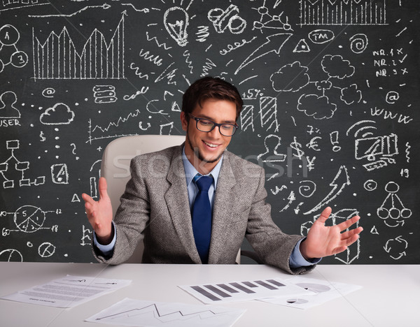 Businessman sitting at desk with business scheme and icons Stock photo © ra2studio
