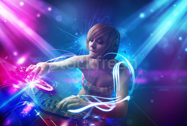 Energetic Dj girl mixing music with powerful light effects Stock photo © ra2studio