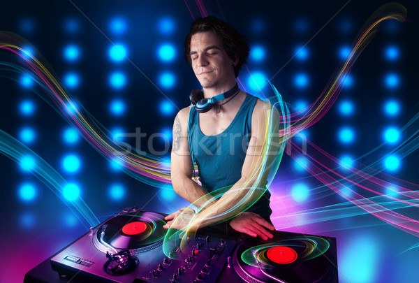 Young Dj mixing records with colorful lights Stock photo © ra2studio