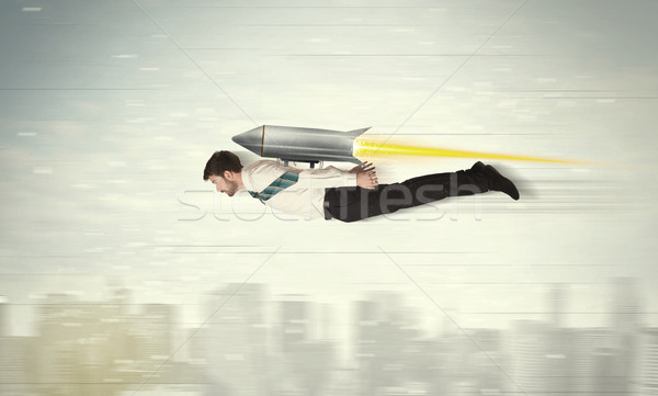 Stock photo: Superhero business man flying with jet pack rocket above the cit