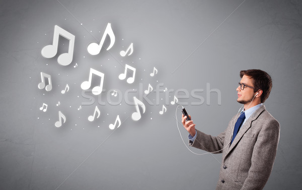Atractivo joven cantando escuchar música notas musicales fuera Foto stock © ra2studio