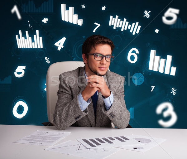 Businessman sitting at desk with diagrams and statistics Stock photo © ra2studio