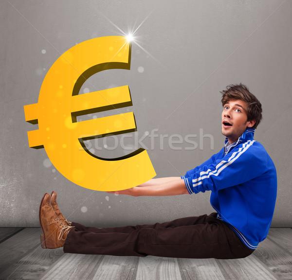 Good-looking boy holding a big 3d gold euro sign Stock photo © ra2studio