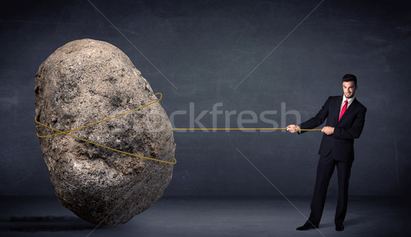 Businessman pulling huge rock with a rope  Stock photo © ra2studio