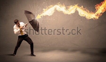 Business man defending himself from a fire arrow with an umbrell Stock photo © ra2studio