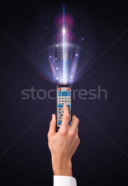 Mão controle remoto brilhante números cartas Foto stock © ra2studio