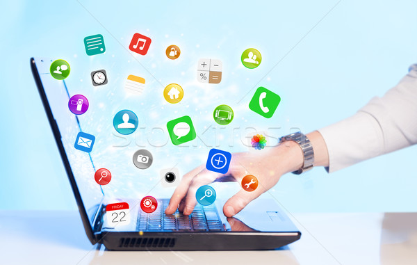 Hand pressing modern laptop with mobile app icons and symbols Stock photo © ra2studio