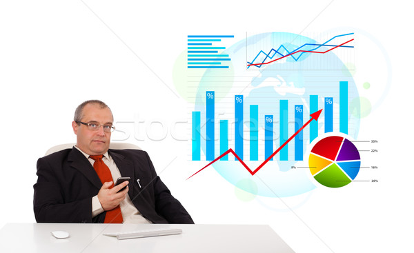 Businessman sitting at desk with statistics and holding a mobilephone, isolated on white Stock photo © ra2studio