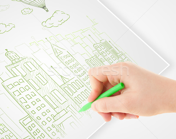 A person drawing sketch of a city with balloons and clouds on a plain paper