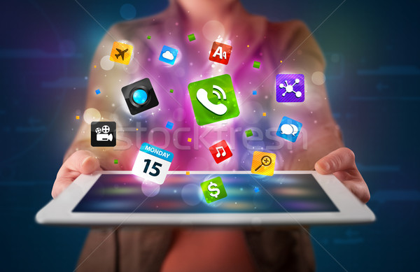 Lady holding a tablet with modern colorful apps and icons Stock photo © ra2studio