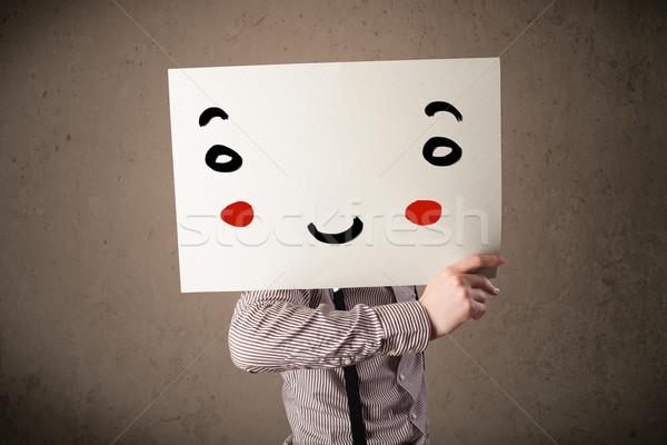 üzletember tart karton mosolygós arc fiatal kéz Stock fotó © ra2studio