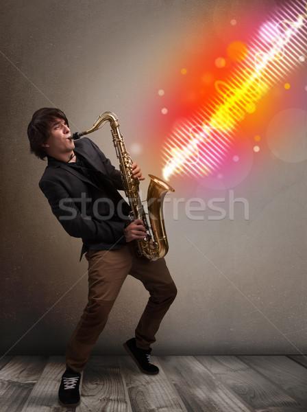 Fiatalember játszik szaxofon színes hang hullámok Stock fotó © ra2studio