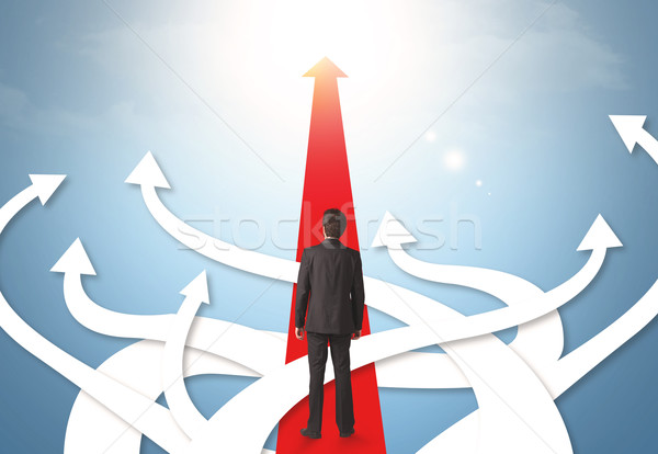 Stock photo: businessman with different direction arrows