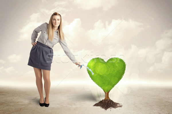Business woman watering heart shaped green tree Stock photo © ra2studio