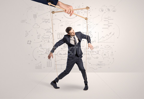 Little businessman controlled from above by another big hand Stock photo © ra2studio