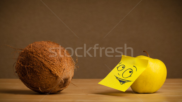 Apple with post-it note looking curiously at coconut Stock photo © ra2studio