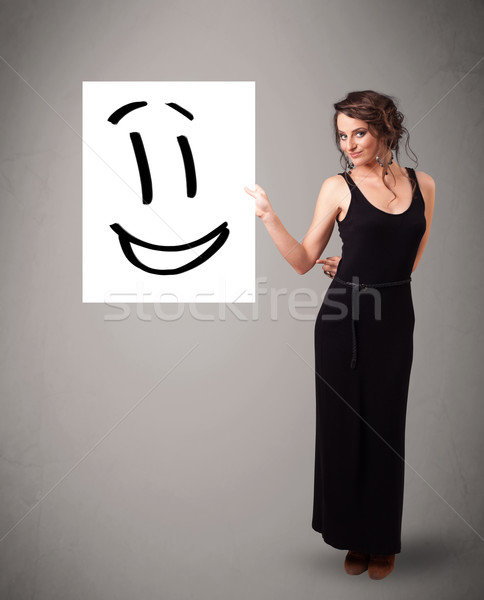 Young woman holding smiley face drawing Stock photo © ra2studio
