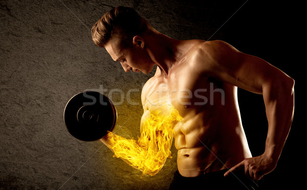 Muscular bodybuilder lifting weight with flaming biceps concept Stock photo © ra2studio