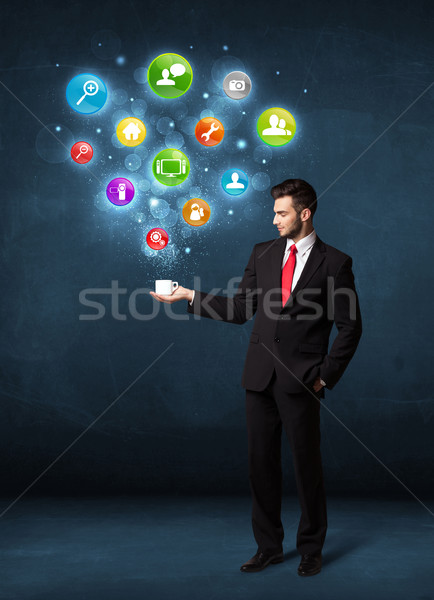 Businessman holding a white cup with setting icons Stock photo © ra2studio