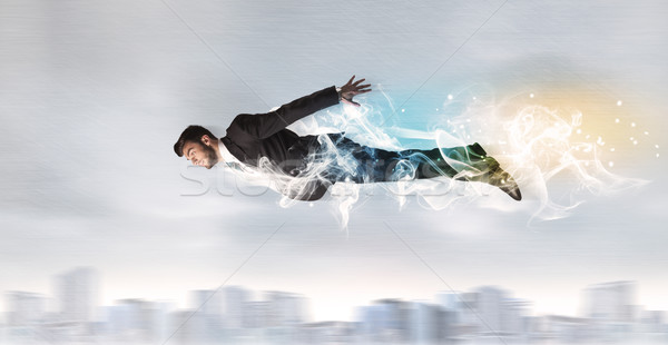 Hero superman flying above city with smoke left behind Stock photo © ra2studio
