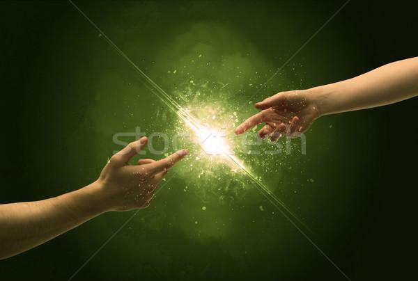 Touching arms lighting spark at fingertip Stock photo © ra2studio