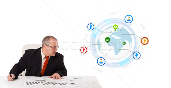 businessman sitting at desk with a globe and social icons Stock photo © ra2studio