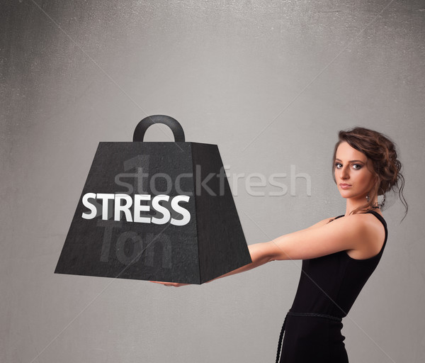 Young woman holding one ton of stress weight Stock photo © ra2studio