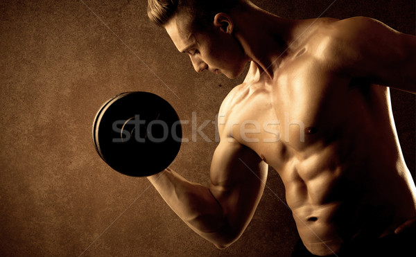 Muscular fit bodybuilder athlete lifting weight  Stock photo © ra2studio