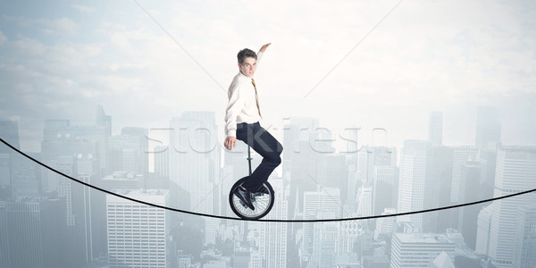 Brave guy riding a monocycle on a rope above cityscape Stock photo © ra2studio