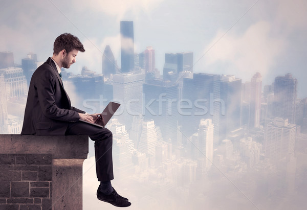 Sales person sitting on top of a tall building Stock photo © ra2studio
