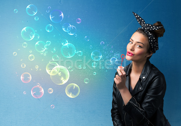 Stock photo: Pretty lady blowing colorful bubbles on blue background