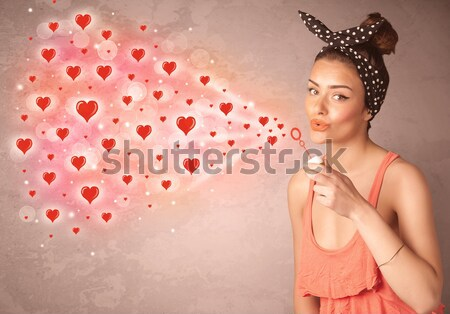 Pretty young girl blowing red heart symbols  Stock photo © ra2studio