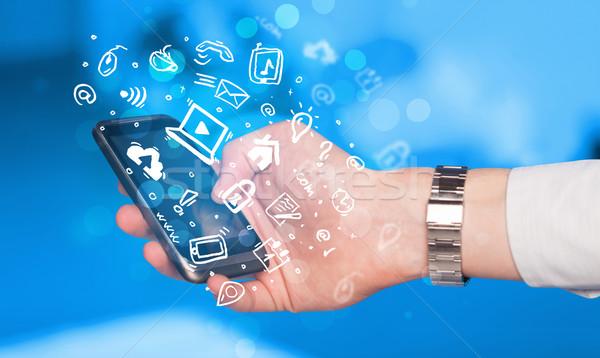 Hand holding smartphone with media icons and symbol  Stock photo © ra2studio