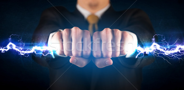 Business man holding electricity light bolt in his hands Stock photo © ra2studio