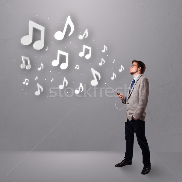 attractive young man singing and listening to music with musical notes Stock photo © ra2studio