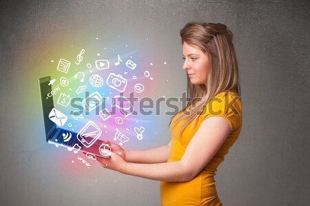 Beautiful young woman holding notebook with colorful hand drawn multimedia icons Stock photo © ra2studio
