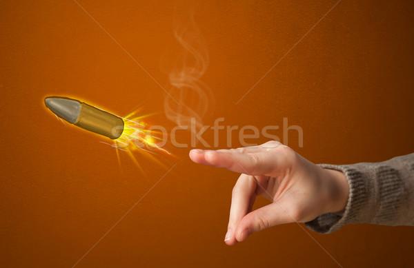 Gun shaped woman hand with bullet Stock photo © ra2studio