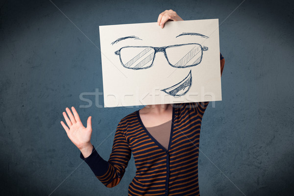 Woman holding a paper with smiley face in front of her head Stock photo © ra2studio