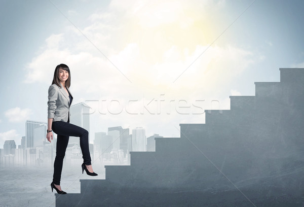 Businesswoman climbing up a concrete staircase concept Stock photo © ra2studio