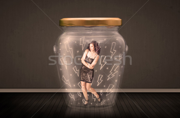 Businesswoman inside a glass jar with lightning drawings concept Stock photo © ra2studio
