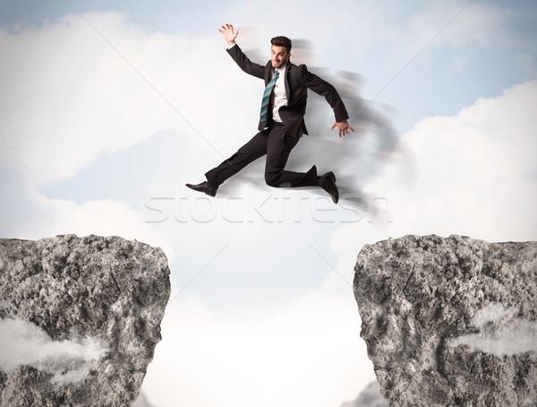 Funny hombre de negocios saltar rocas brecha negocios Foto stock © ra2studio