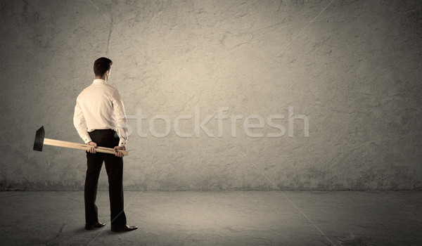 Business man standing in front of a grungy wall with a hammer Stock photo © ra2studio