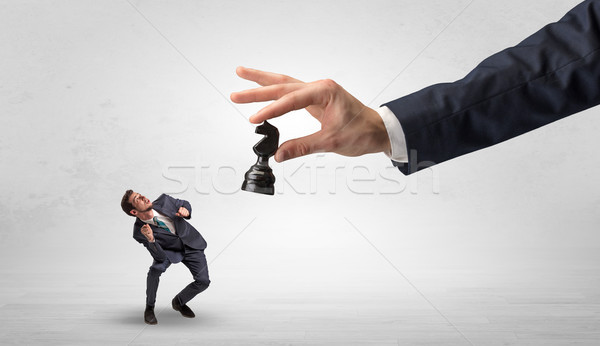 Big hand with chessman down small weak businessman concept Stock photo © ra2studio