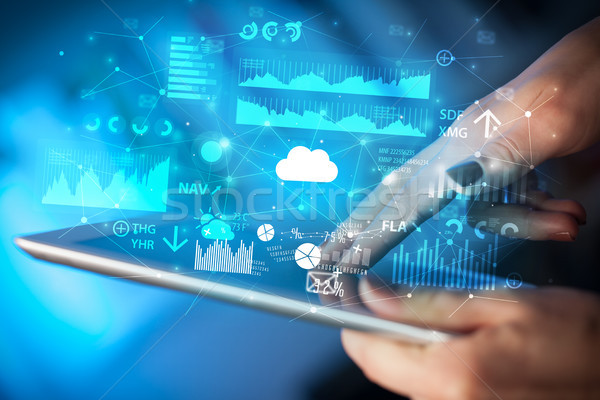 Stock photo: Hand using tablet with application icons flying around