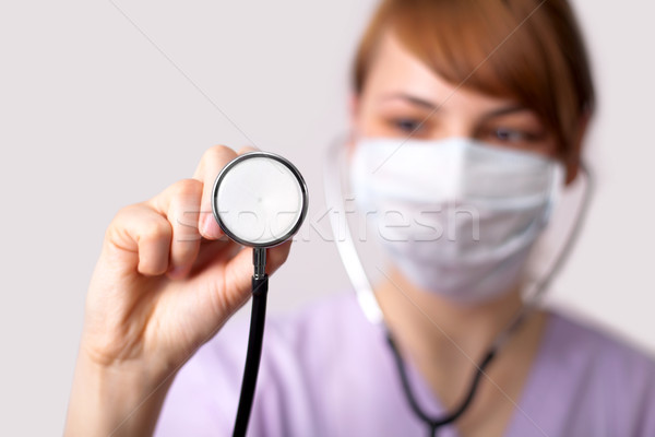 Female doctor holding stethoscope pointed toward camera Stock photo © ra2studio