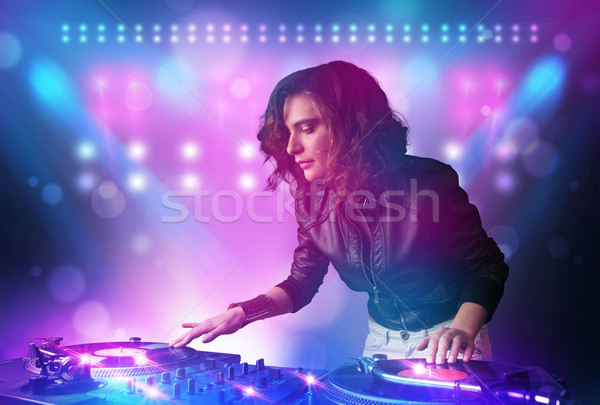 Stock photo: Pretty young disc jockey mixing music on turntables on stage with lights and stroboscopes