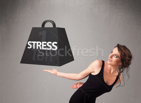 Stock photo: Young woman holding one ton of stress weight