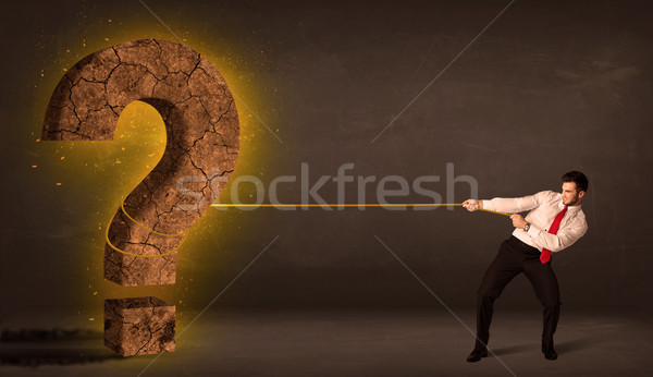 Business man pulling a big solid question mark stone Stock photo © ra2studio