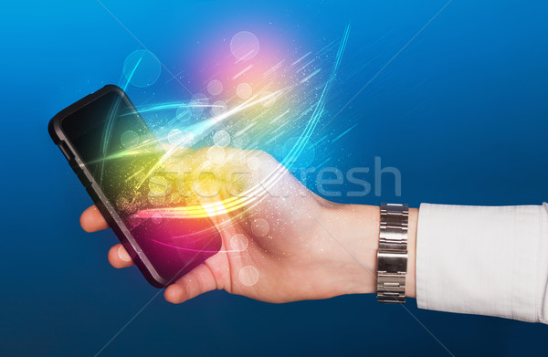 Hand holding smart phone with abstract glowing lines Stock photo © ra2studio